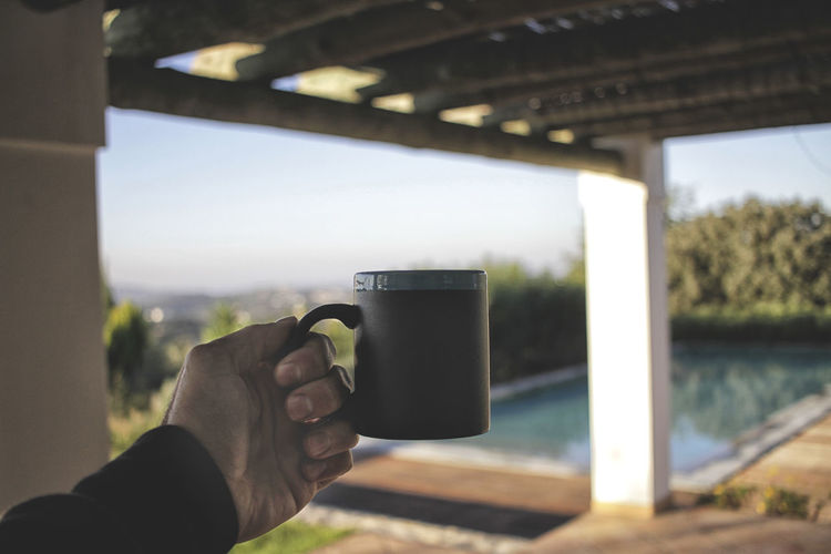 Holding coffee mug in front of beautiful view with swimming pool Holding Coffee Mug Architecture Building Exterior Built Structure Close-up Coffee Mug Communication Day Drink Focus On Foreground Holding Human Body Part Human Hand Leisure Activity Lifestyles Men Nature One Person Outdoors Photographing Photography Themes Real People Sky Water Wireless Technology