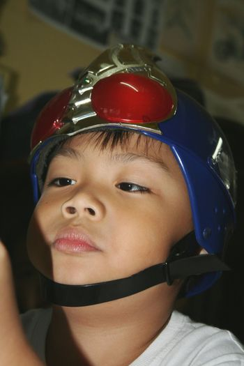 Close-up of cute boy wearing helmet at home
