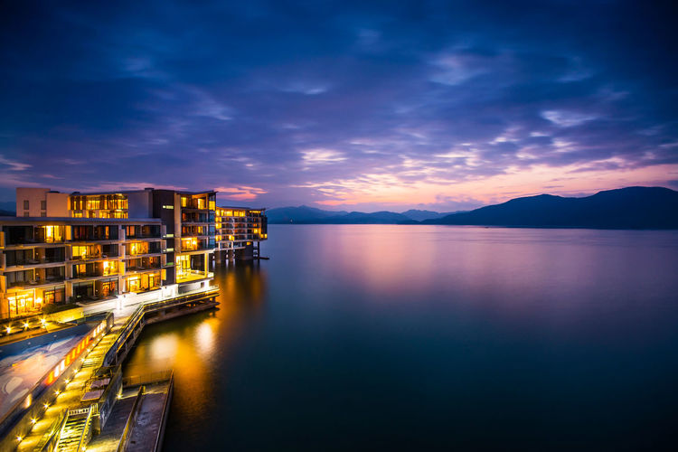 Illuminated Hotel By Lake Against Cloudy Sky At Dusk