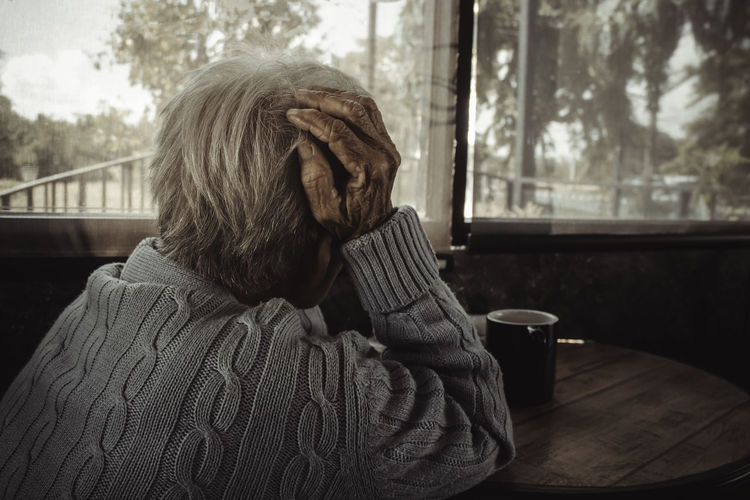 Adult woman, old person has a headache. concept loneliness, dementia, abuse, sadness, healthcare.