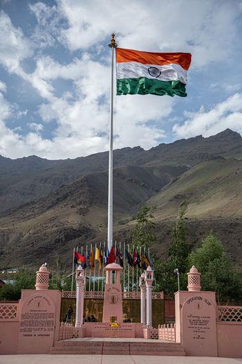 Flag by temple against sky