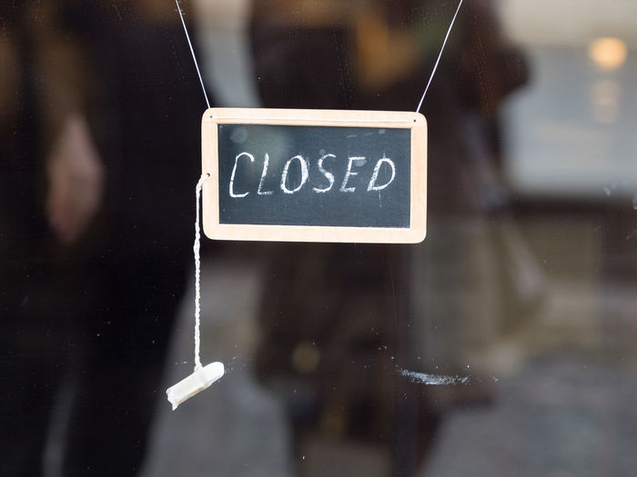 Close-Up Of Closed Text On Blackboard Hanging At Store