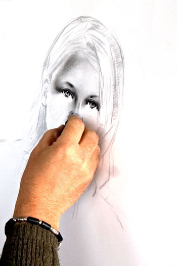 An artist making a charcoal drawing on the white paper. Human Body Part Body Part Human Hand Hand Adult Human Face One Person Portrait White Background Looking At Camera Women Covering Human Eye Young Adult Aggression  Finger Fear Violence Hopelessness Drawing Charcoal Charcoal Drawing Eyes Artist Painter