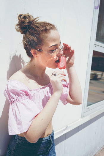 Young Woman Licking Flavored Ice Against Wall