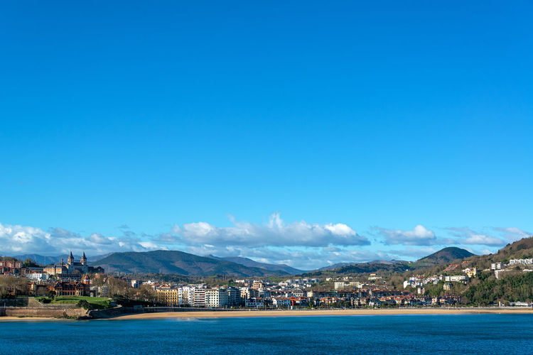Scenic view of sea by townscape against sky