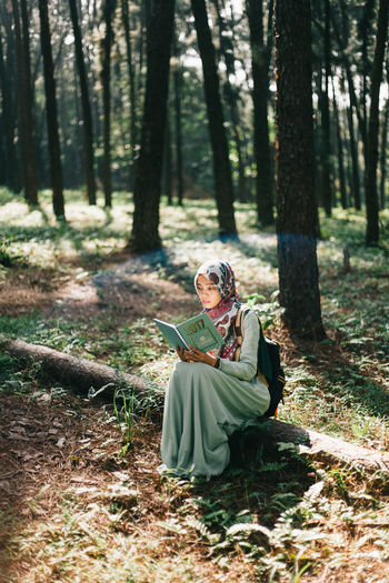 Woman wearing hijab reading book while sitting in forest
