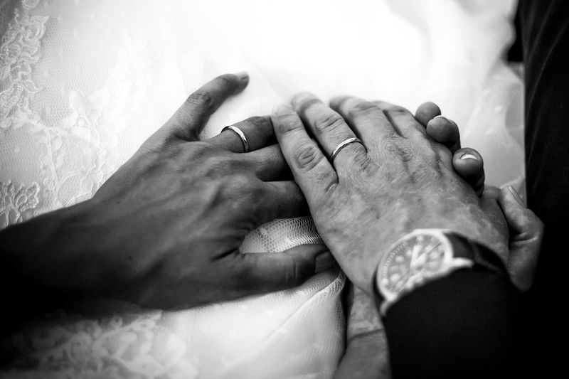 Cropped image of bride and groom holding hands
