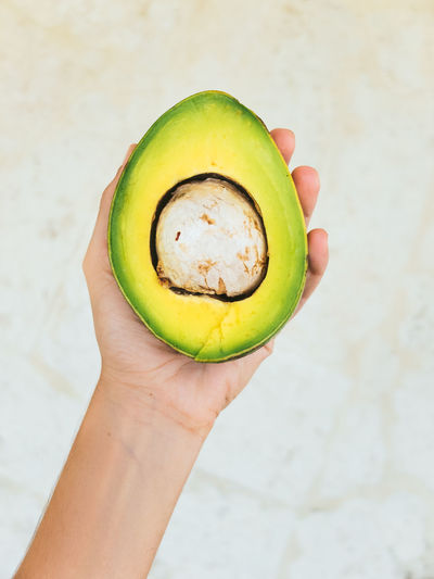 Cropped image of hand holding avocado against white wall