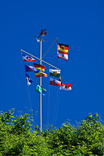 Low angle view of various colorful flags against clear blue sky