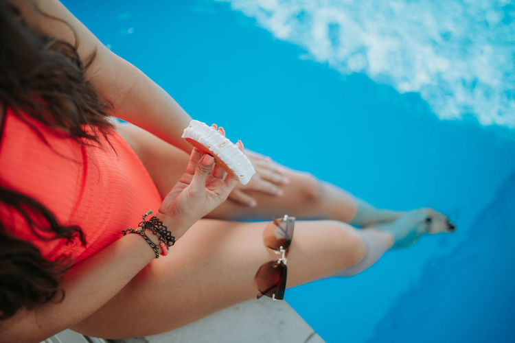 Midsection of woman holding hands in swimming pool