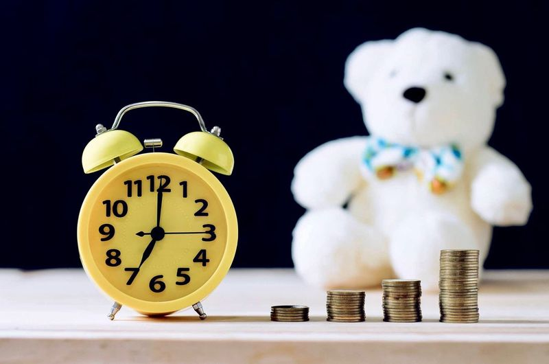 Stacked coins and alarm clock with teddy bear on table