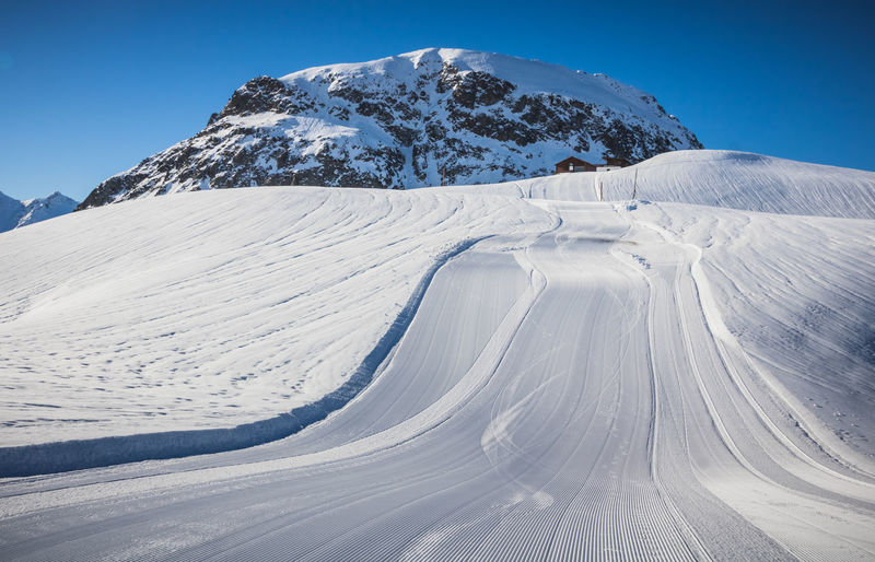Snow covered mountain and empty ski slope against sky