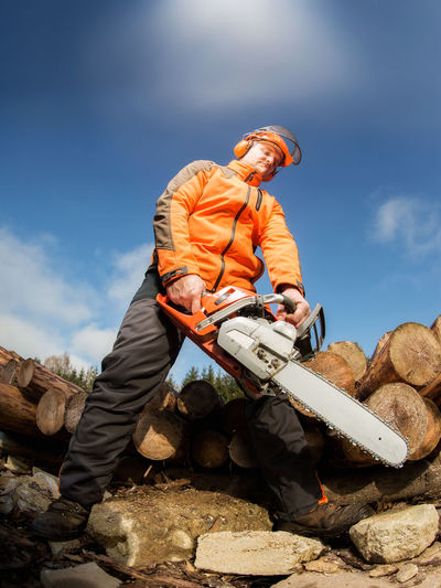 Low Angle View Of Lumberjack Cutting Wood Against Sky