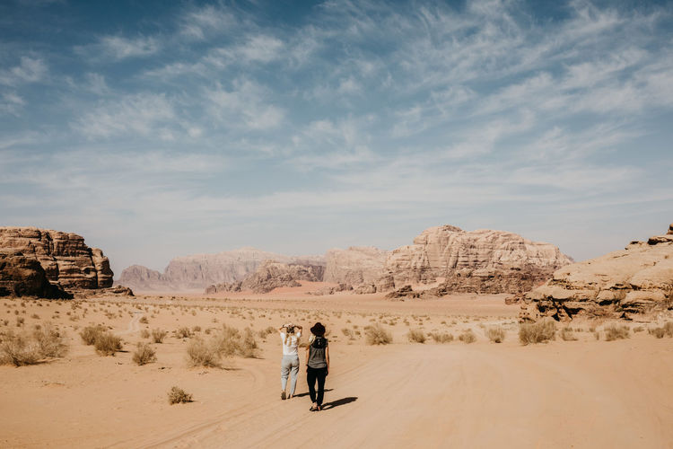 Rear view of couple standing on rock in desert against sky