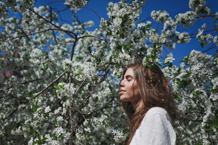 Side view of young woman standing against flower tree