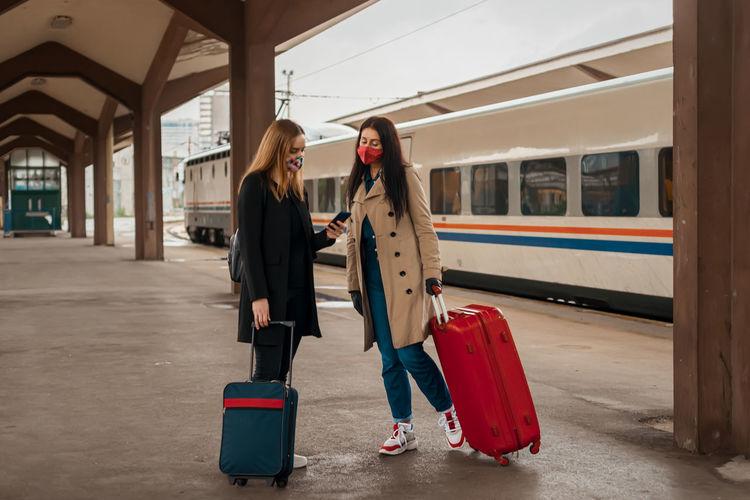 Full length of women wearing mask holding suitcase standing on railroad platform