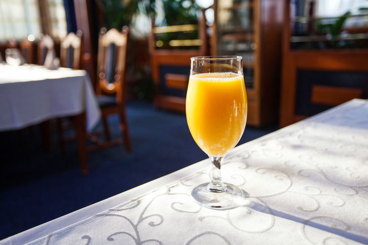 glass of orange juice at the table Glass Juice Orange Table Drink Restaurant Tasty Refreshing Beverage Vitamin Juicy Closeup Citrus  Glassware Delicious Natural Yellow Tablecloth Healthy Freshness Breakfast Cocktail Nobody Fruit Interior