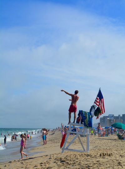 Man gesturing while standing on lifeguard chair at beach against sky