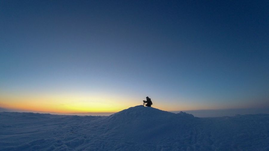 Man crouching on snow covered landscape against clear sky during sunset