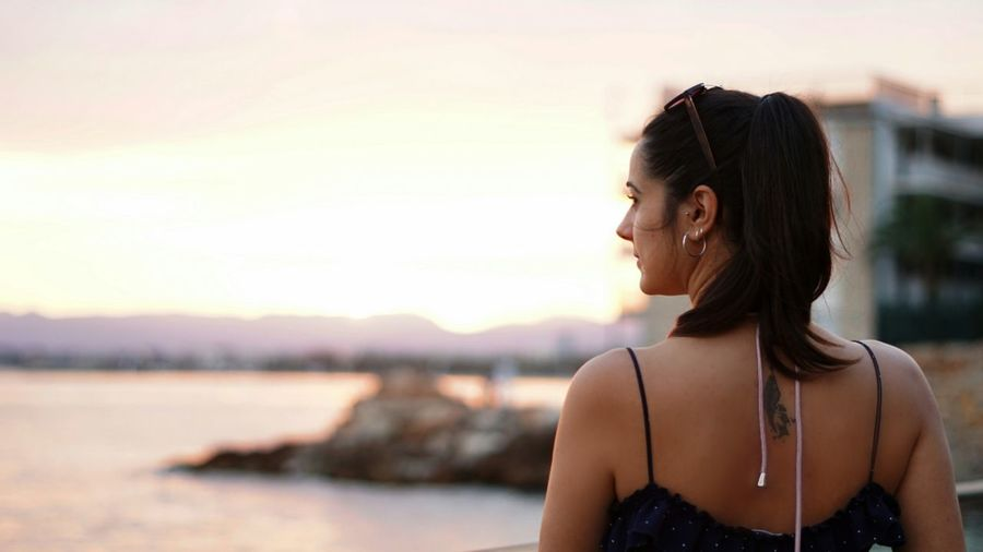 Portrait of smiling young woman looking away againts sea at sunset