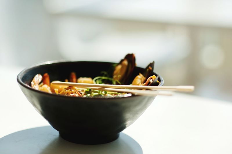 close-up of a young man eating an asian food dish Bowl Food And Drink Food Focus On Foreground Indoors  Healthy Eating Wellbeing Day Indulgence Ready-to-eat Serving Size Kitchen Table No People Still Life Freshness Vegetable Close-up Meal Japanese Food