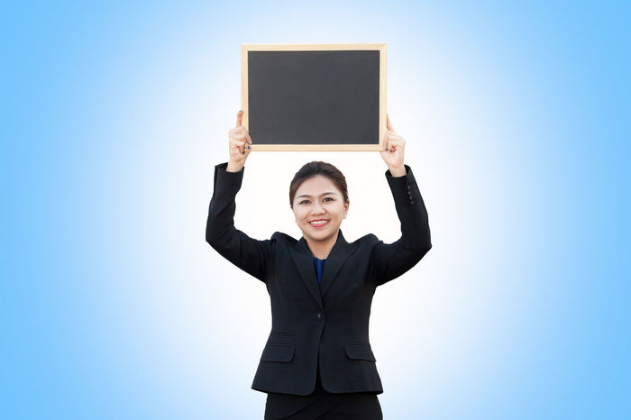 Business woman holding empty blackboard Advertising Asian  Isolated Thai Woman Advert Advertisement Background Billboard Black Blackboard  Board Business Businesswoman Chalkboard Concept Copy Space Corporate Business Holding Looking At Camera Overhead People Portrait Smiling Suit