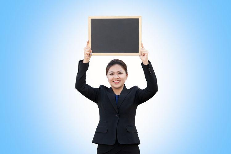 Portrait of smiling businessman holding blank blackboard against blue background