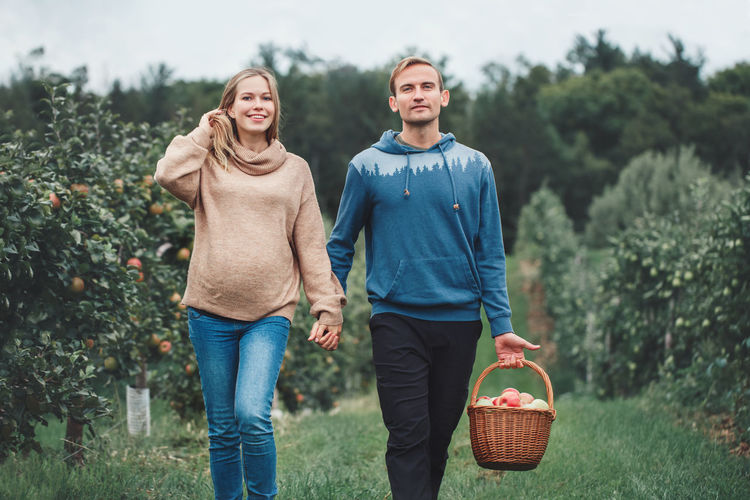 Portrait of smiling pregnant woman with husband walking on land