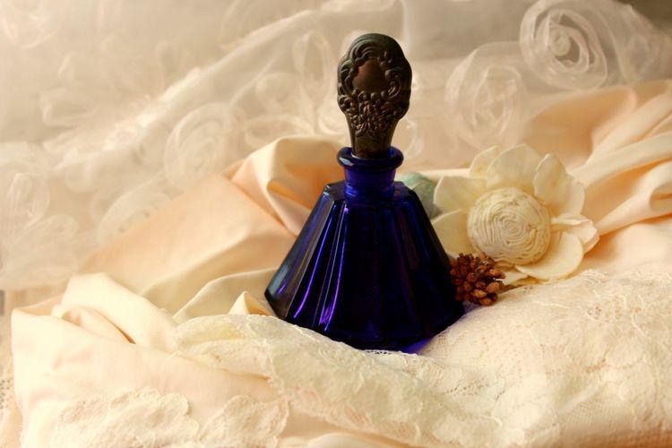 Close-up of perfume bottle on dress