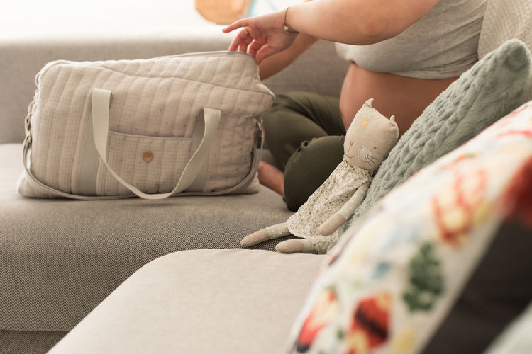 Low section of woman relaxing on sofa at home