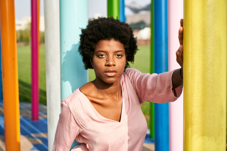 Portrait of young woman with curly hair standing against colorful columns