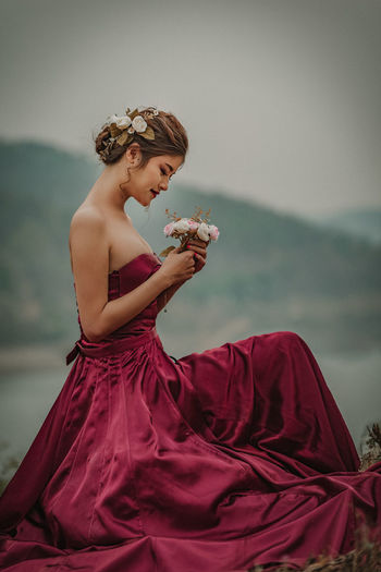 Side View Of Young Woman Holding Flowers While Sitting Against Sky
