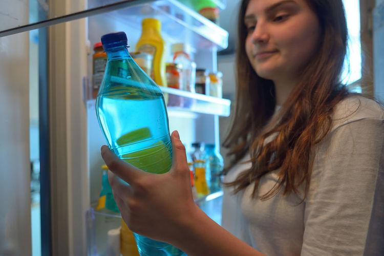 Teenage girl removing bottle from refrigerator