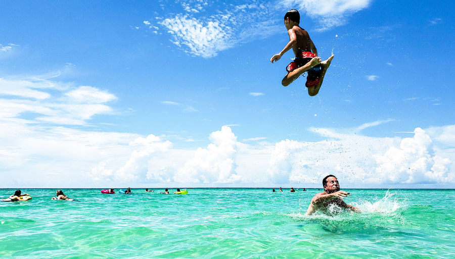 Boy jumping above man swimming in sea
