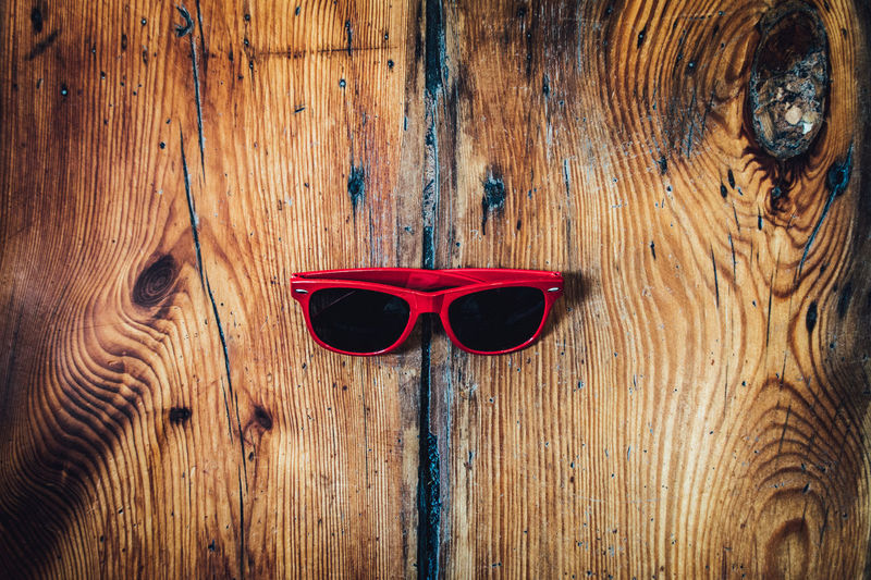 Directly Above View Of Red Sunglasses On Wooden Table