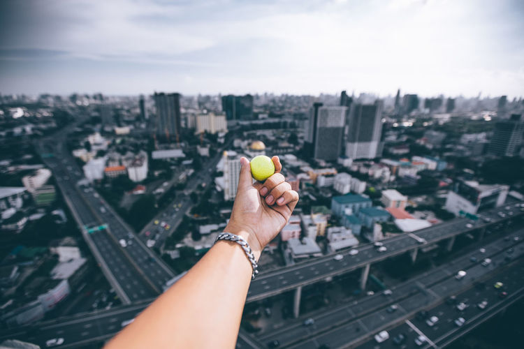 Cropped Hand Holding Ball Over Cityscape