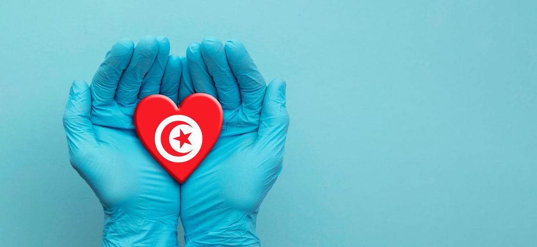 Close-up of hand holding heart shape against blue background