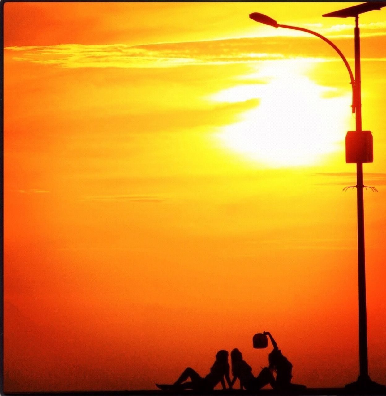 sunset, orange color, silhouette, nature, real people, yellow, outdoors, sky, beauty in nature, scenics, lifestyles, photography themes, photographing, men, technology, one person, day, people
