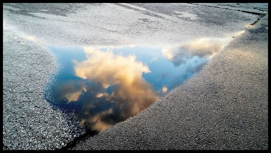 The sky meets the ground in a melted puddle of snow pn a truck stop parking lot.