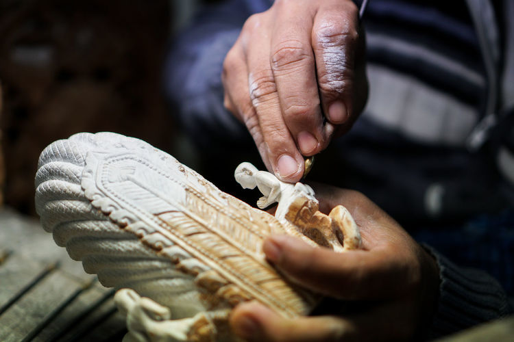 Close-up of man working on small religious sculpture