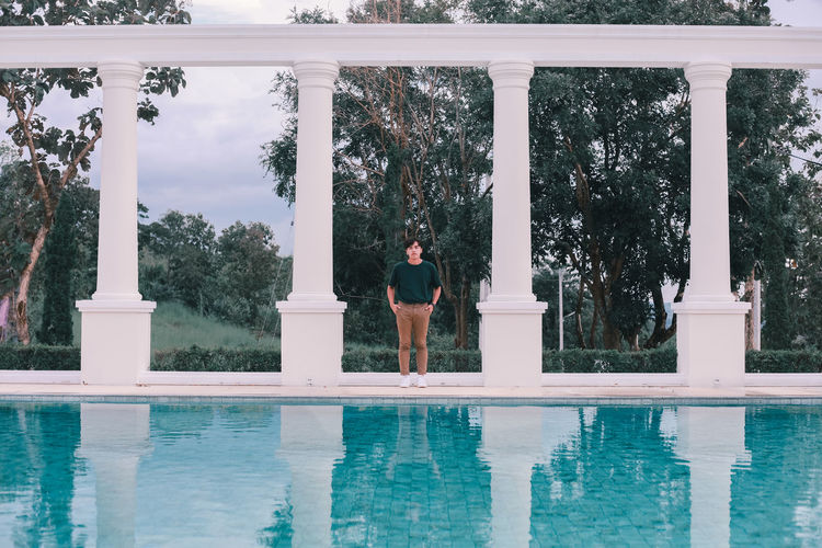 Reflection of man standing on swimming pool