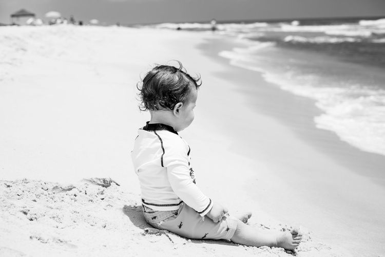 Side view of boy sitting on shore at beach during sunny day