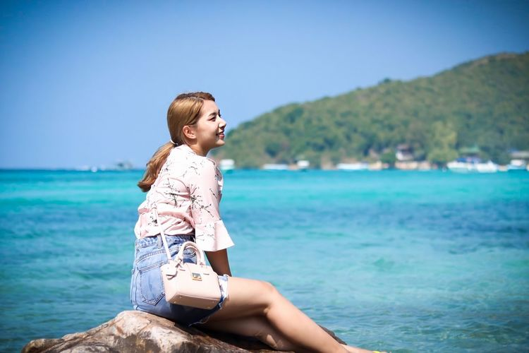 Young woman sitting on rock by sea