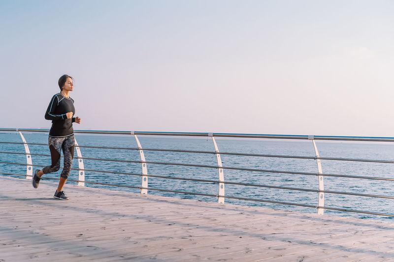 Full length of man standing on railing against sea