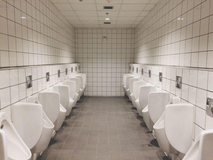 Urinals in illuminated public restroom