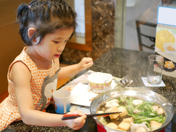 Cute girl eating food at home