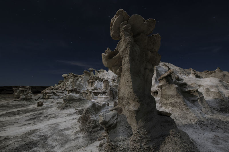 Low angle view of statue on rock against sky