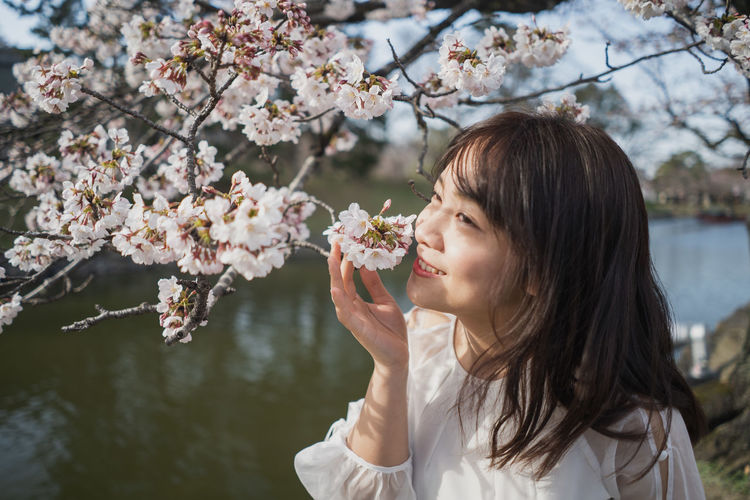 Young woman holding cherry blossoms in spring