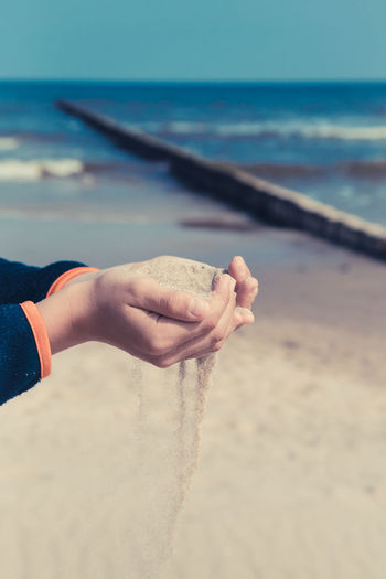 Midsection of person holding sand on beach