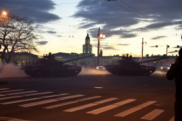 Cars on road in city against sky during sunset